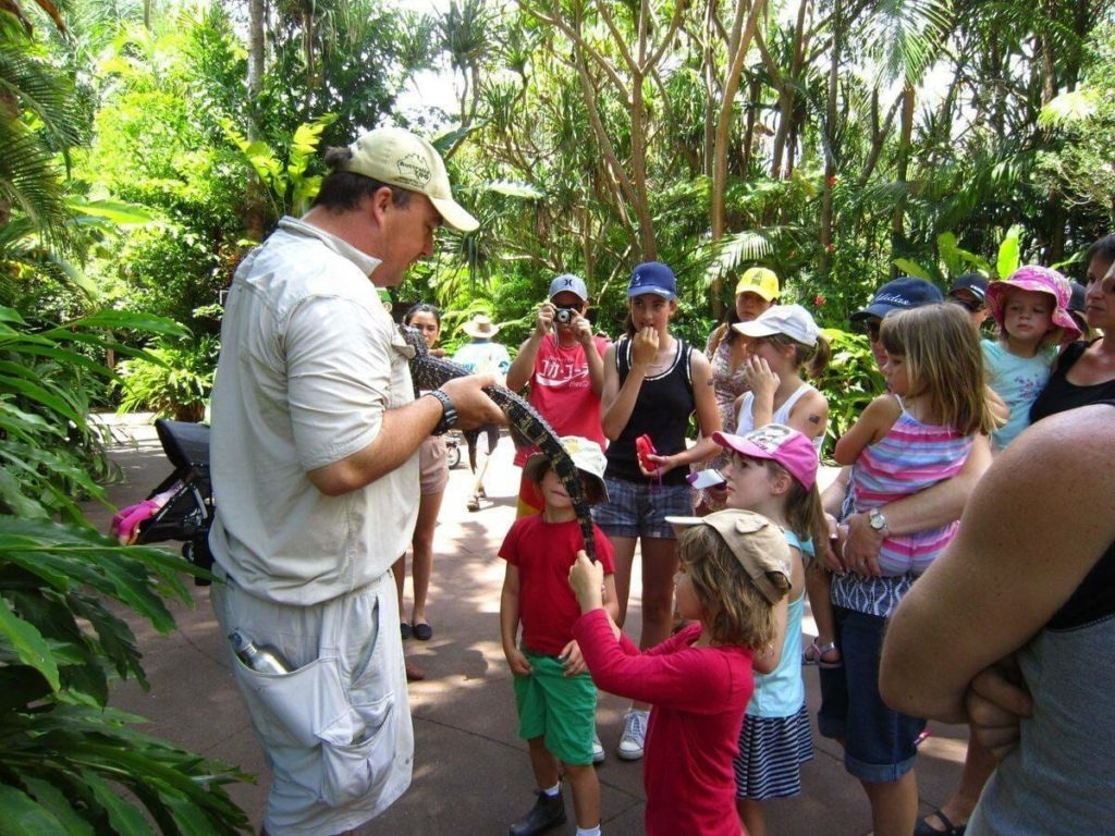 Ranger holds lizard in front of crowd of kids at Australia Zoo