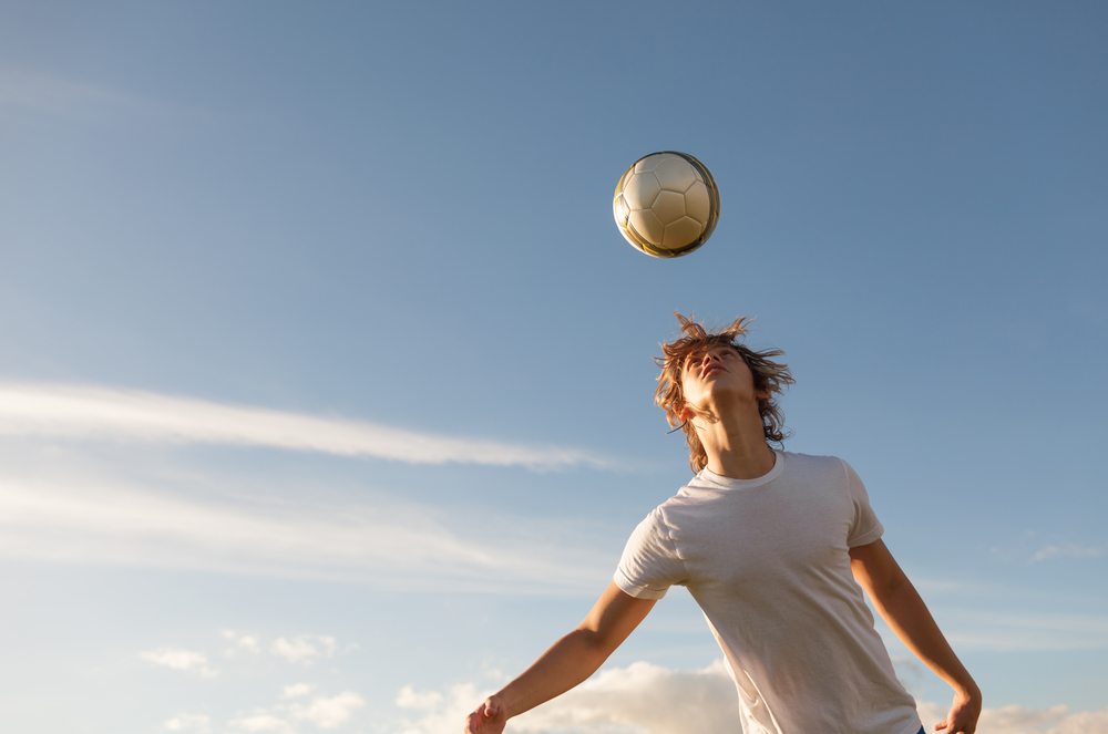 teenager bouncing a soccer ball from his head