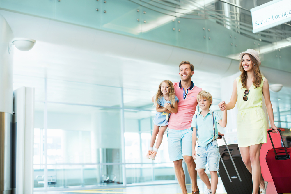 family walking through the airport with luggage