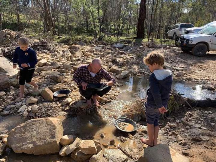 A father and two sons try their luck gold panning on a creek near Bathurst